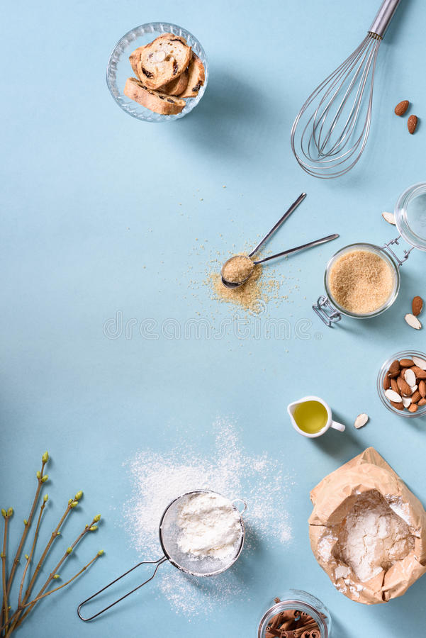 Cooking and baking ingredients - egg, flour, brown sugar, almonds over blue table. Spring theme. Top view, copy space, stock photo