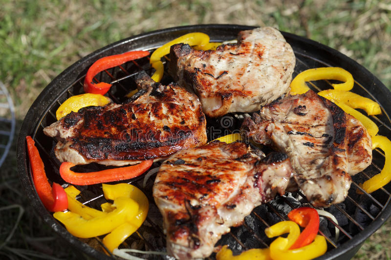 Cooking barbecue pork loin and pepper. On a barbecue grill royalty free stock photo