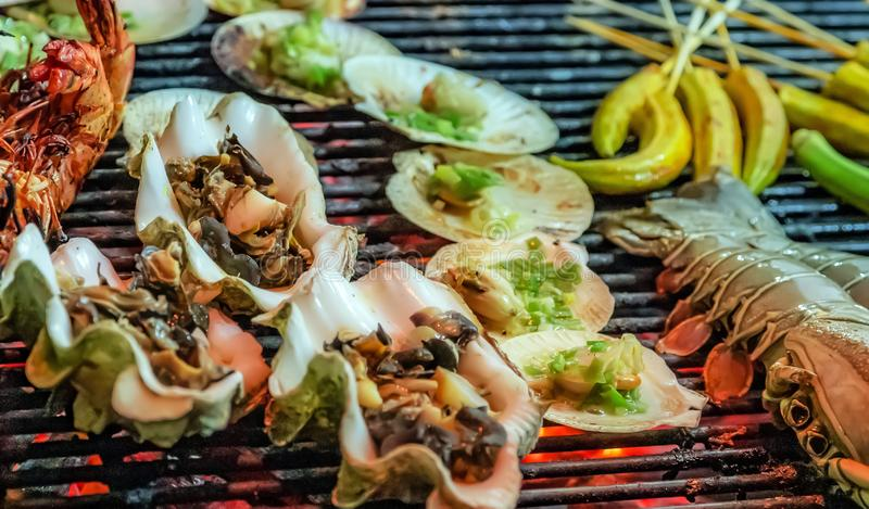 Cooking bbq scallop seashell muscle mussel oyster. Mix scallop seashell muscle mussel oyster flaming charcoal grill with open fire grilling barbecue steamed royalty free stock image