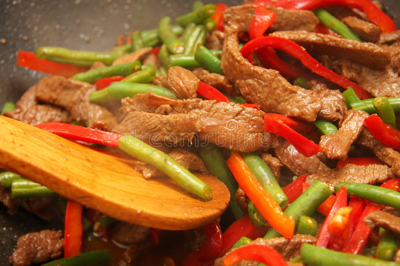 Cooking beef, capsicum and bean stirfry in wok