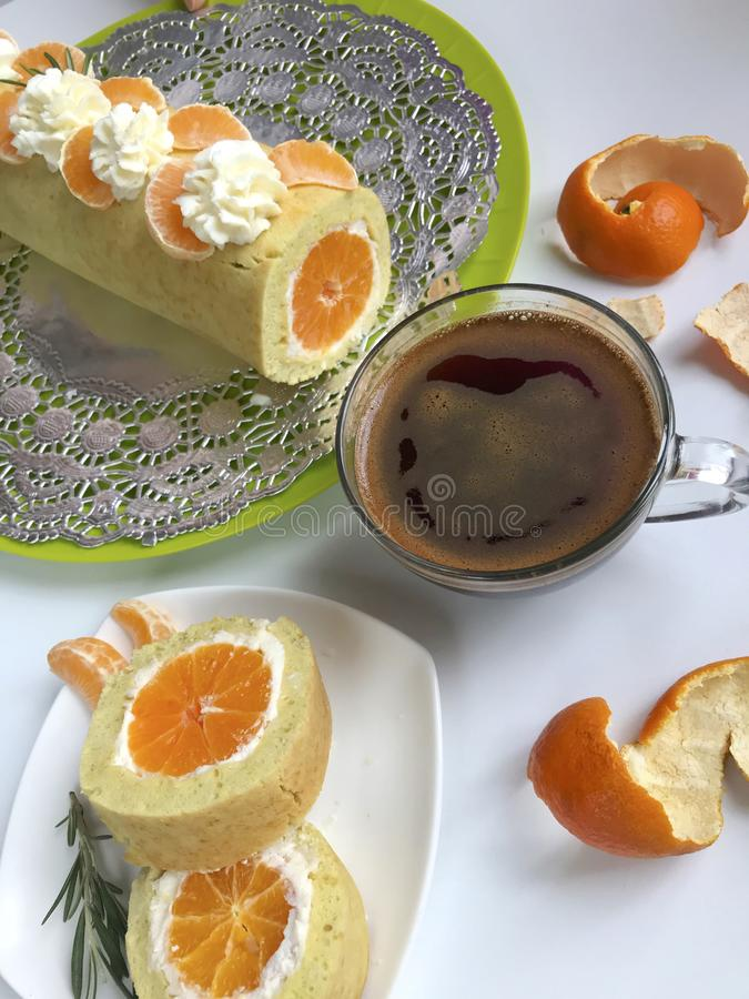 Cooking biscuit roll stuffed with ricotta and mandarin. Ready roll lies on a platter. Next on the saucer is a cut piece of roll.  royalty free stock photography