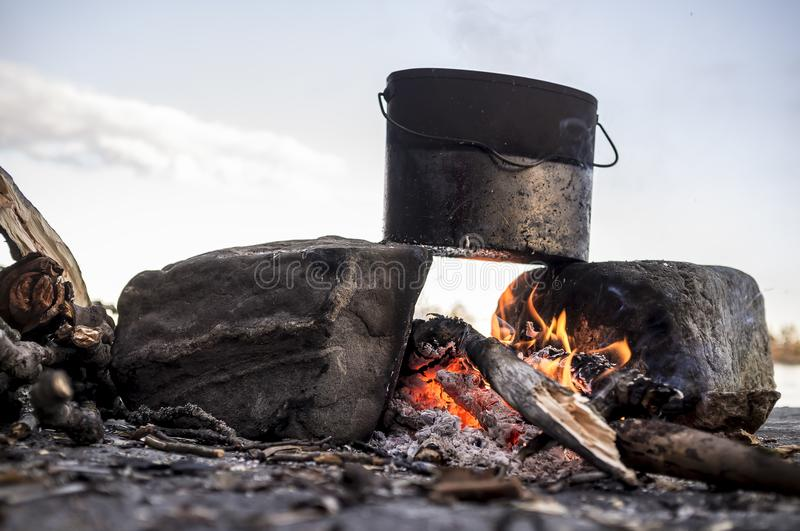 Cooking with a bowler that stands on two stones and a fire between them, against the sky and sunset. stock photo
