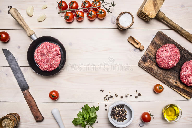 Cooking burgers, ground beef in a small frying pan with herbs and cherry tomatoes a branch, a knife for mea place for text,fram stock photos
