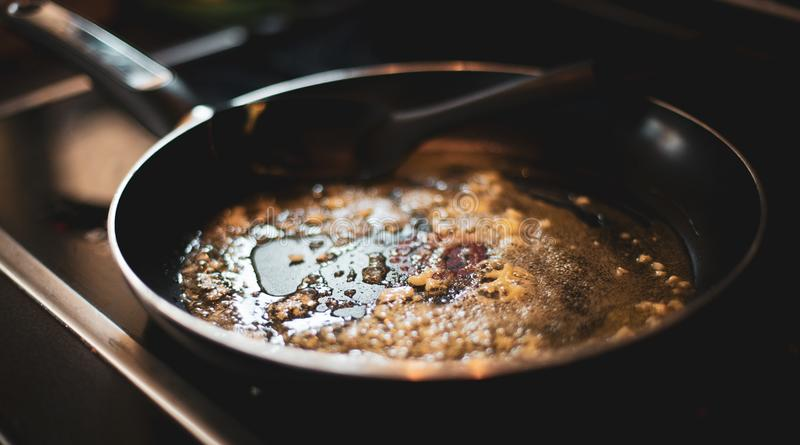 Cooking Butter and Garlic in a black pan royalty free stock images
