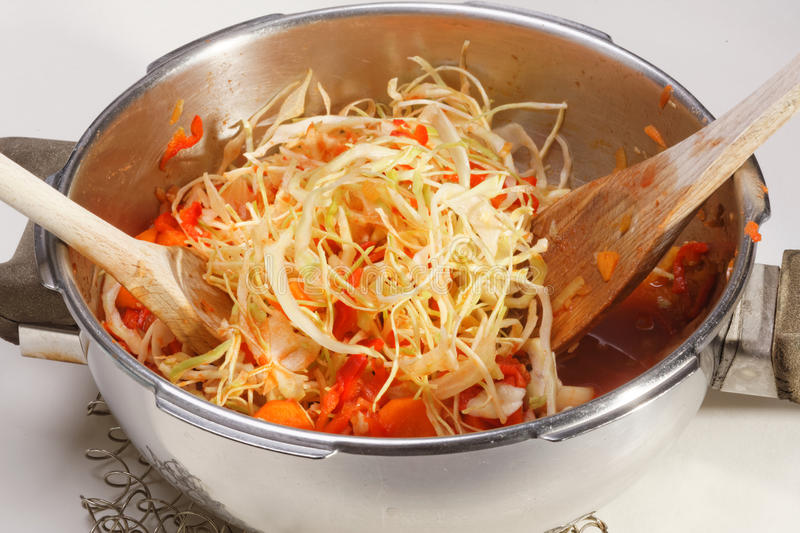 Cooking Cabbage and Red Peppers. Shredded cabbage and red peppers in metal cooking pot being stirred with wooden spoons royalty free stock photography
