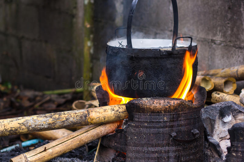 Cooking in cauldron licked by flames on open fire fi. Close up of cooking in cauldron licked by flames on open fire fireplace made of bricks stones in field royalty free stock photo