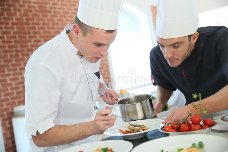Cooking chef giving students cooking skills royalty free stock photo