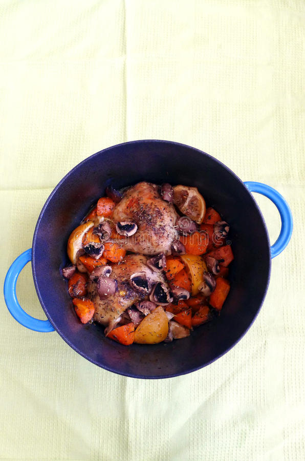 Cooking chicken in cast iron pot stock image