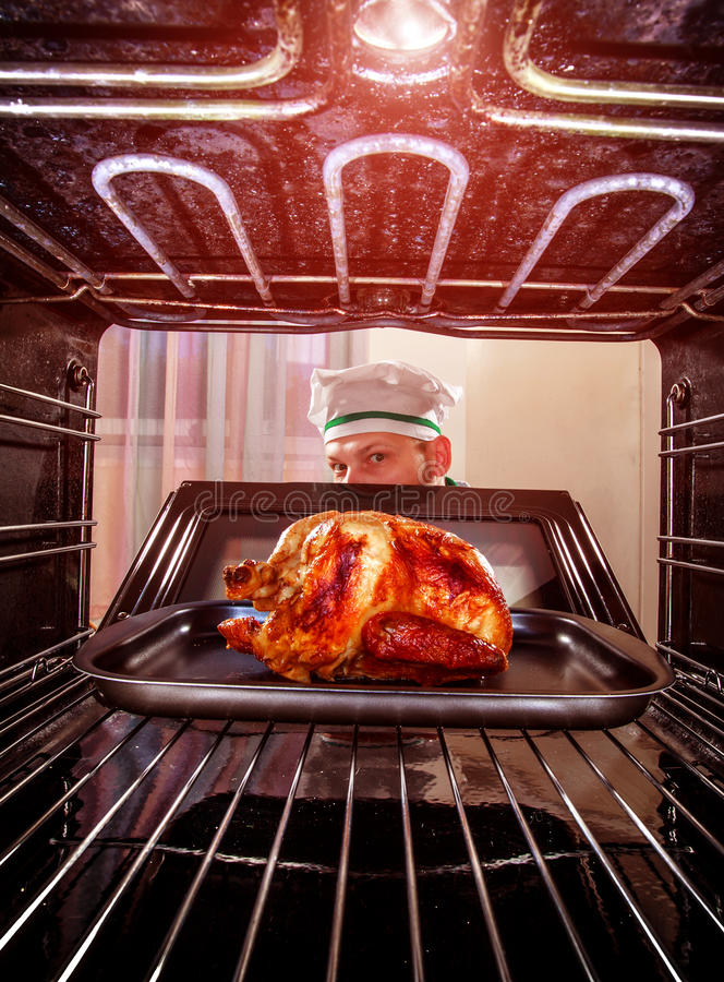 Cooking chicken in the oven. royalty free stock images