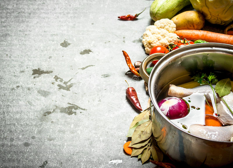 Cooking chicken soup with vegetables in a large pot. royalty free stock photography