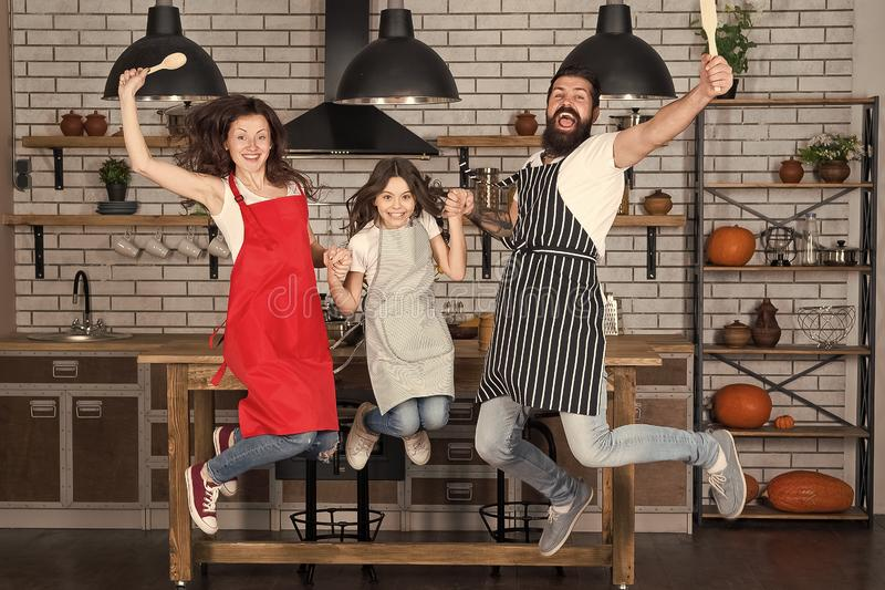 Cooking with child might be fun. Having fun in kitchen. Family mom dad and little daughter wear aprons jump in kitchen. Family having fun cooking together royalty free stock image