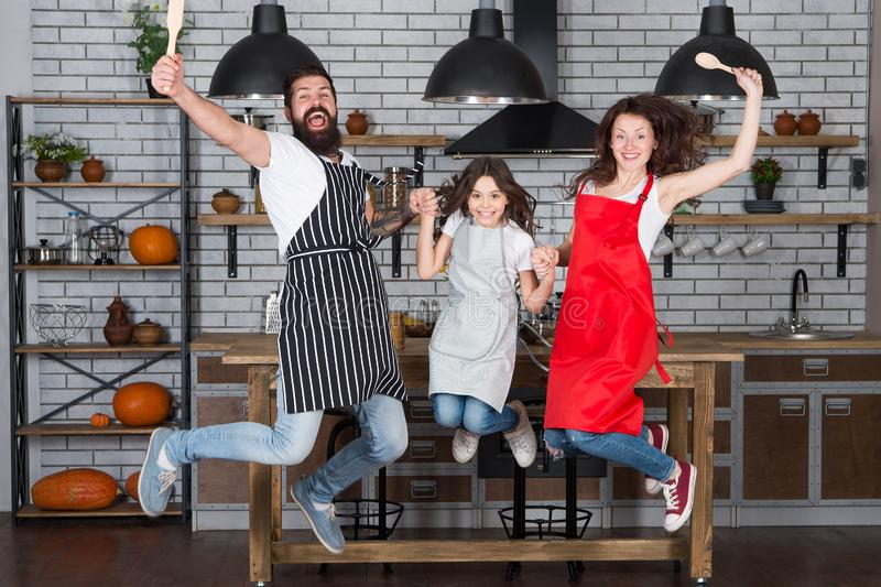 Cooking with child might be fun. Having fun in kitchen. Family mom dad and little daughter wear aprons jump in kitchen. Family having fun cooking together stock images