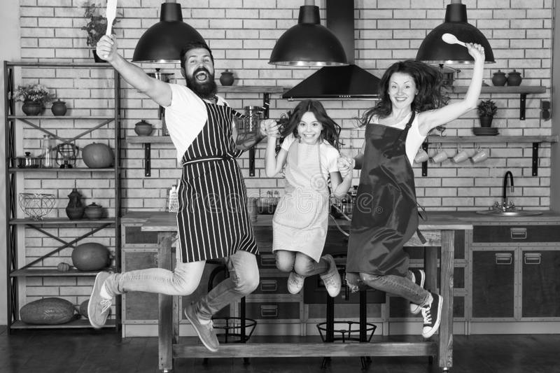 Cooking with child might be fun. Having fun in kitchen. Family mom dad and little daughter wear aprons jump in kitchen. Family having fun cooking together stock photography