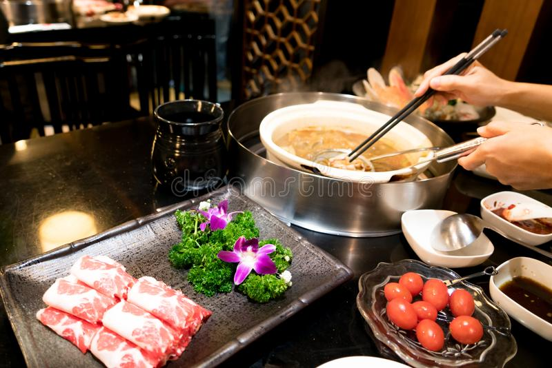 Cooking Chinese shabu with cherry tomato and yummy beef meat royalty free stock images