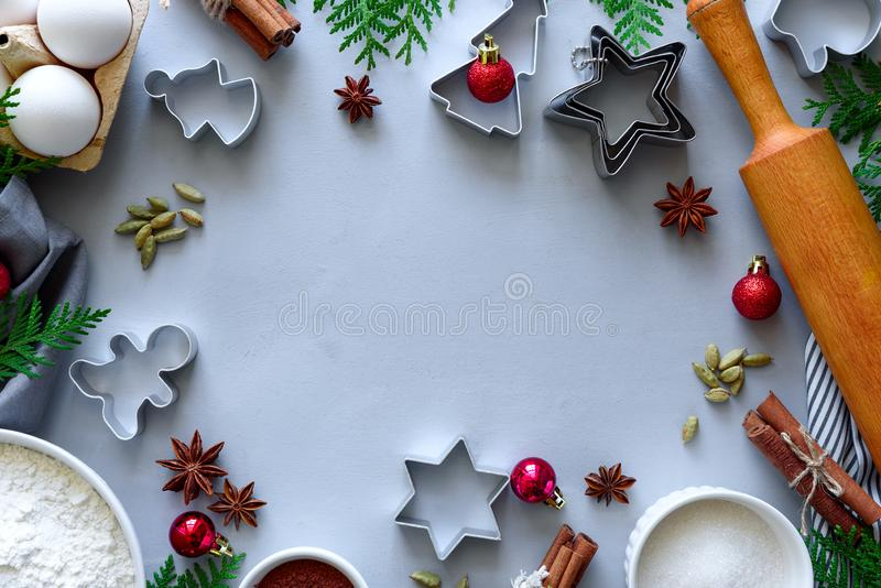 Cooking Christmas cookies. Ingredients for gingerbread dough: flour, eggs, sugar, cocoa, cinnamon sticks, anise stars and cookie. Cutters on gray wooden stock image