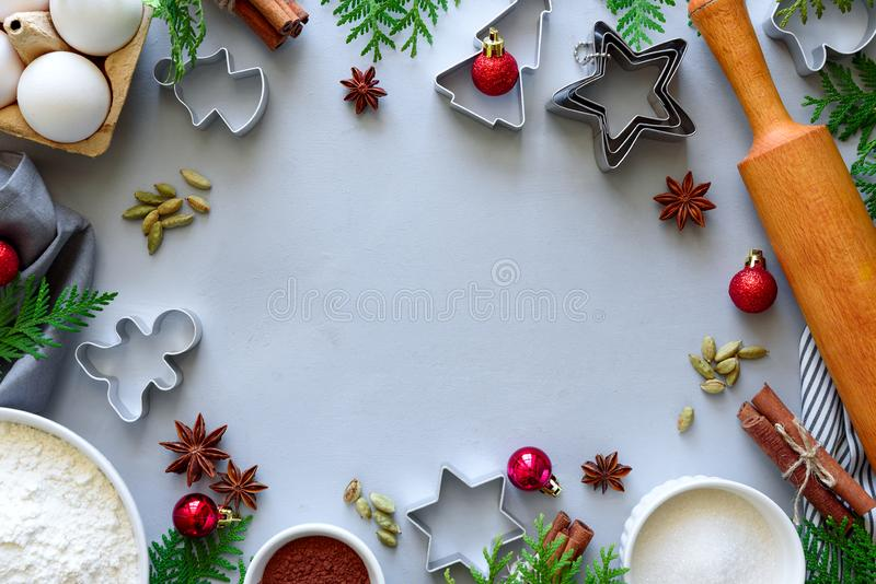 Cooking Christmas cookies. Ingredients for gingerbread dough: flour, eggs, sugar, cocoa, cinnamon sticks, anise stars and cookie. Cutters on gray wooden stock photos