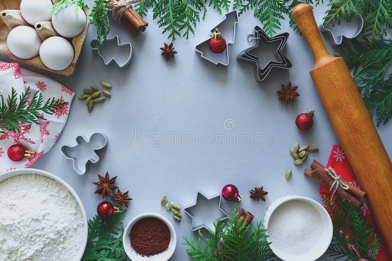 Cooking Christmas cookies. Ingredients for gingerbread dough: flour, eggs, sugar, cocoa, cinnamon sticks, anise stars and cookie. Cutters on gray wooden royalty free stock image