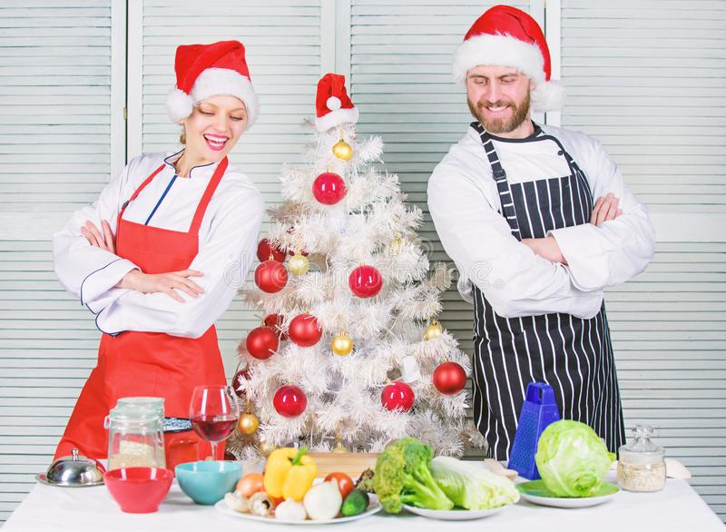 Cooking christmas meal. Man and woman chef apron santa hat near christmas tree. Christmas recipe concept. Secret stock photo
