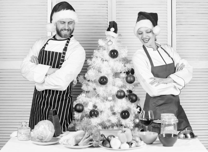 Cooking christmas meal. Man and woman chef apron santa hat near christmas tree. Christmas recipe concept. Secret royalty free stock photos