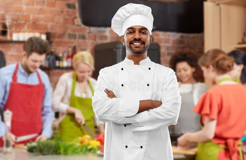 Happy male indian chef in toque at cooking class. Cooking class, profession and people concept - happy male indian chef in toque over group of students stock photography