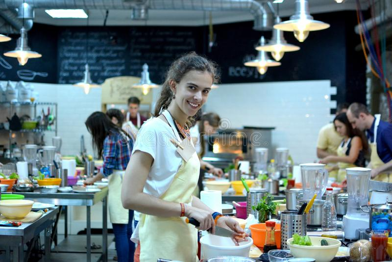 Cooking class. young happy friends in the kitchen royalty free stock photography