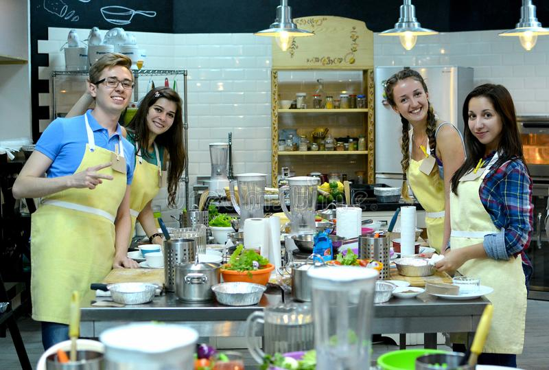 Cooking class. young happy friends in the kitchen royalty free stock images