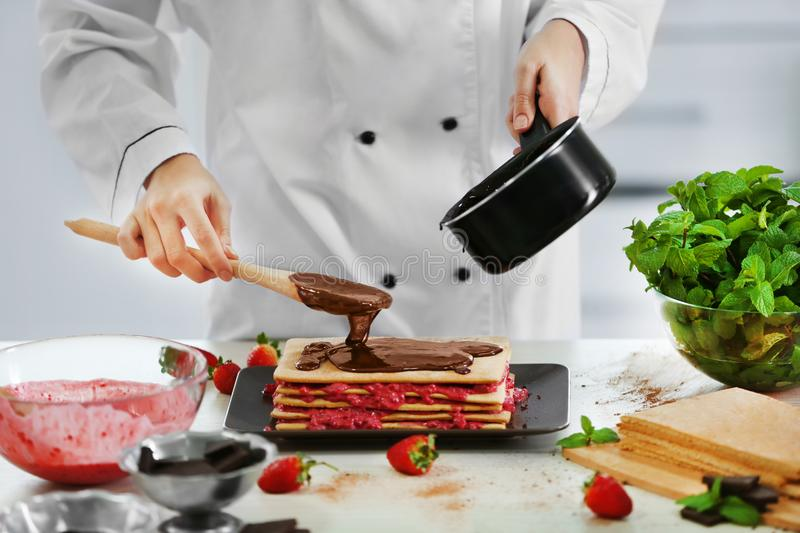 Cooking concept. Professional confectioner decorating delicious cake with chocolate frosting, stock photography