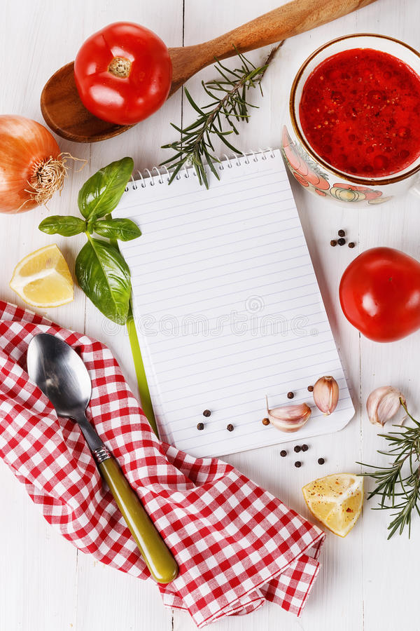 Cooking concept. Recipe book and ingredients for cooking tomato. Soup over white wooden background. Top view stock images