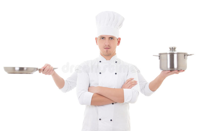 Cooking concept - young man in chef uniform with four hands hold. Ing saucepan and frying pan isolated on white background stock photography