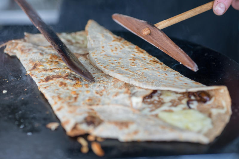 Cooking Crepe on Skillet Being Folded. Crepe on hot griddle being folded using wooden scraper and trowel royalty free stock image