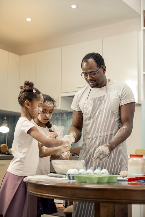 Father wearing striped apron feeling amazing cooking with daughters. Cooking with daughters. Father wearing striped apron feeling amazing cooking with his cute royalty free stock photos