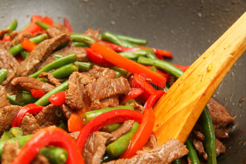 Cooking delicious beef, bean, capsicum stir-fry. In a wok stock image