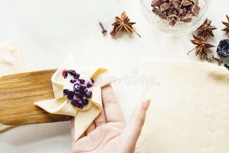 Cooking delicious. Sweets with jam and cinnamon and powder to tea. A woman`s hand holds unfolded unpacked cake and wooden spatula. On white table lies sieve and stock image