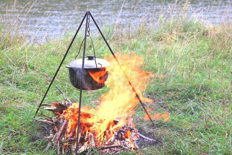 Cooking delicious tasty food outdoors on fire in pot in summer in good weather with wood from forest stock photos