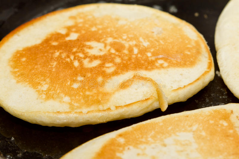Cooking drop scones. Close up of drop scones or pancakes being fried in hot butter royalty free stock photography