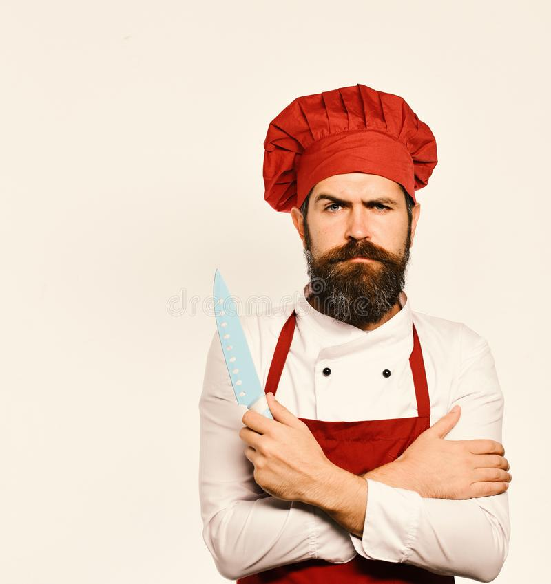 Cooking equipment and cuisine concept. Cook with serious face in burgundy apron and chef hat. stock photography