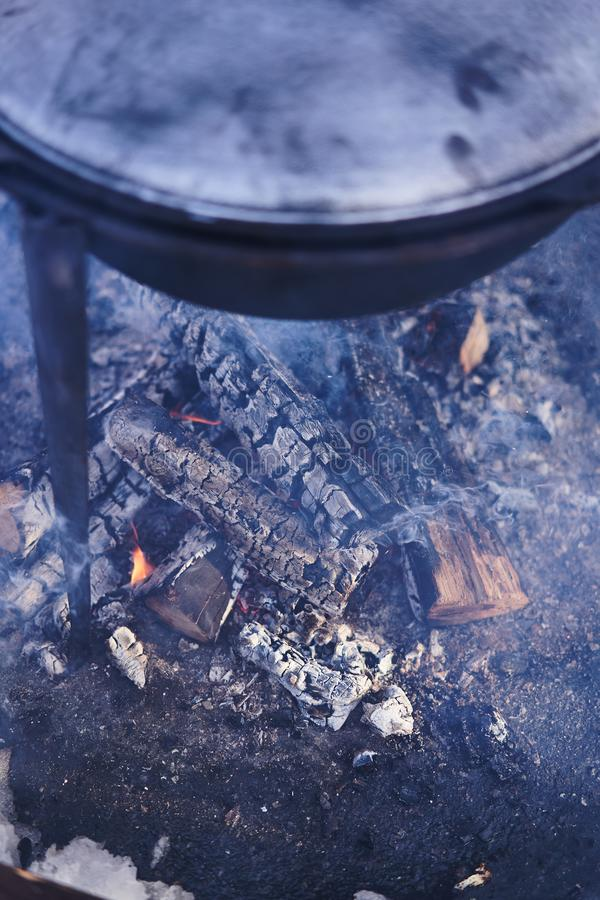 Cooking on a fire. Fish soup on a fire. Food in a cauldron on a fire. Food outdoors. Cooking outdoors stock images