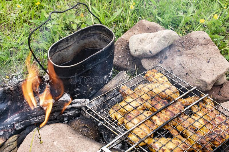 Cooking on the fire food. Chicken shashlik on the grill with tea on the fire royalty free stock photos