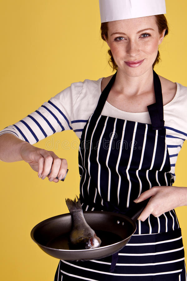 Cooking fish. A young attractive female chef cooking a fish in a pan stock photos