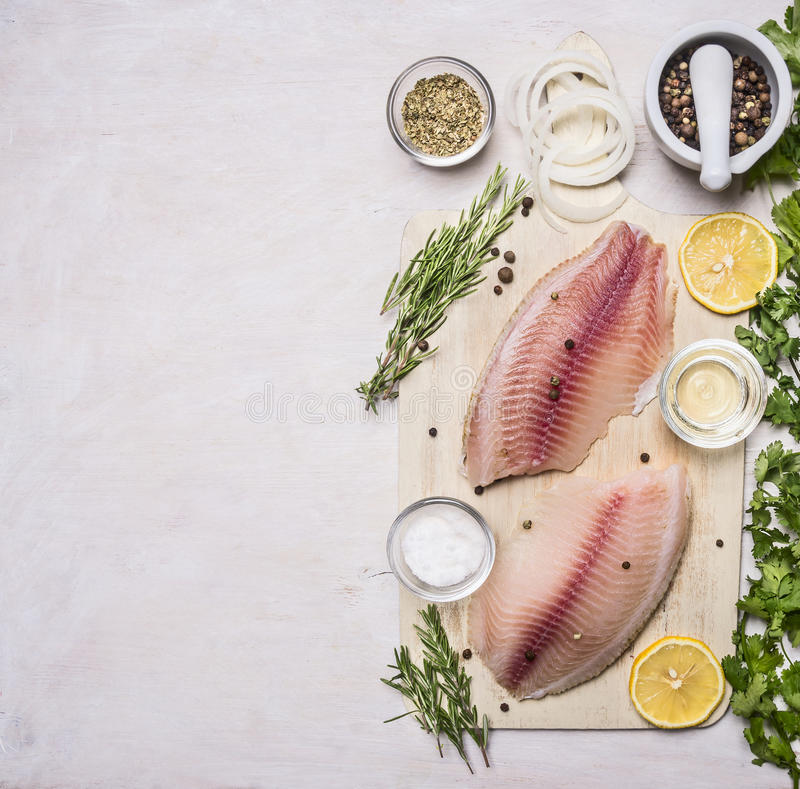 Cooking fish with herbs, butter and lemon, and pepper in mortar border place for text royalty free stock photos