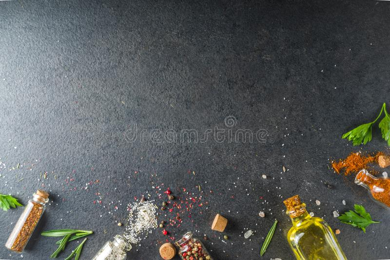 Cooking food background with herbs, olive oil and spices. Black stone concrete background above copy space royalty free stock image