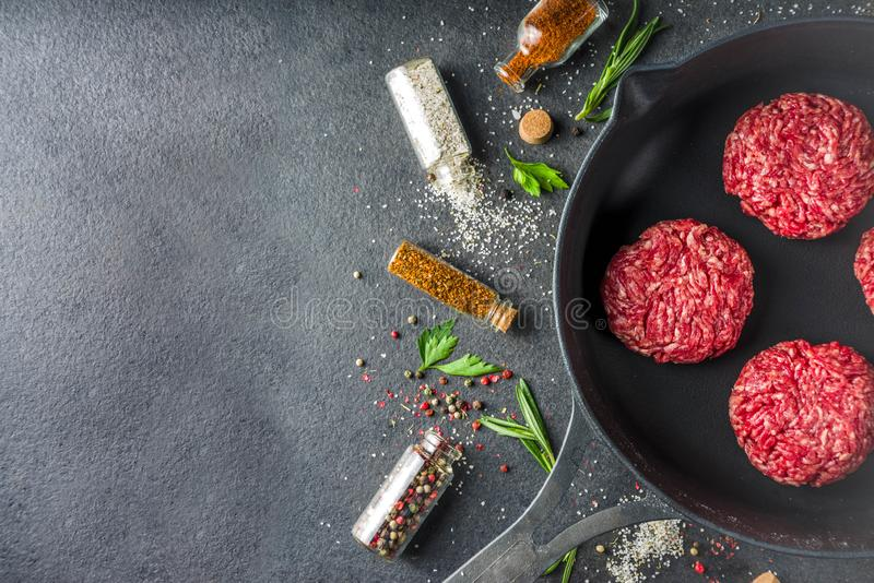 Cooking food background with herbs, olive oil and spices. Black stone concrete background above copy space stock photo