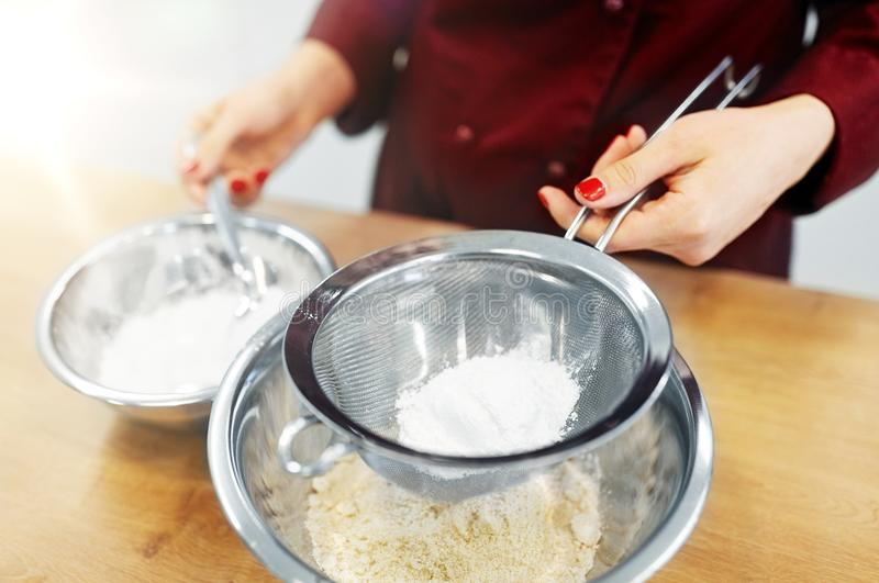 Chef with flour in bowl making batter or dough. Cooking food, baking and people concept - chef with strainer sieving flour into bowl and making batter or dough stock photo