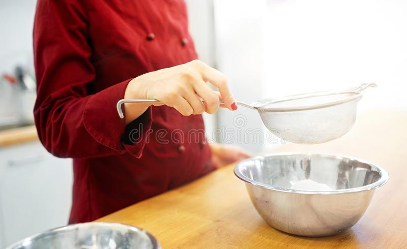 Chef with flour in bowl making batter or dough. Cooking food, baking and people concept - chef with strainer sieving flour into bowl and making batter or dough stock photos
