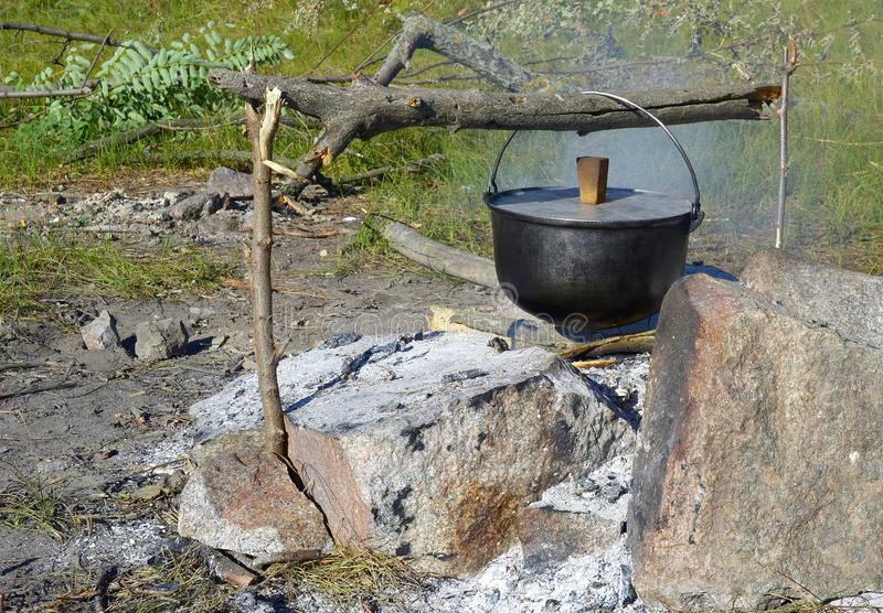 Cooking food in a bowler hat in the open air stock images