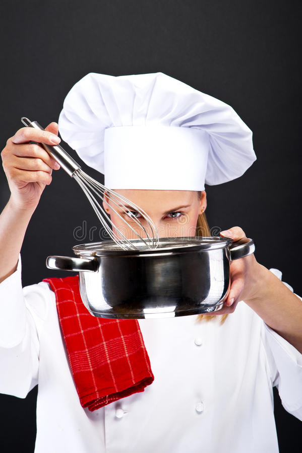Cooking and food concept - female chef with poy and spoon. Cooking and food concept - smiling female chef with poy and spoon tasting food stock photo