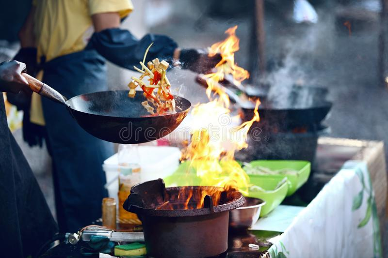 Cooking Food On Fire On Street Festival. Chef Cooking Thai Dish In Wok Outdoors. High Resolution royalty free stock photo