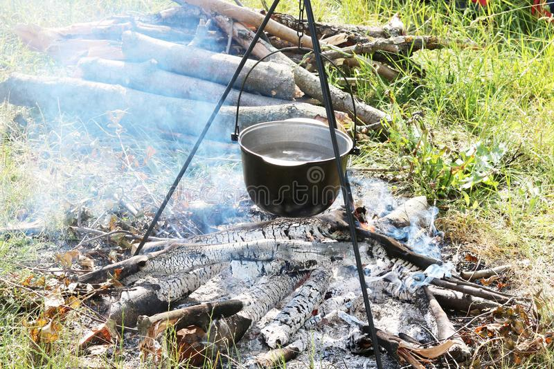 Cooking food in kettle on firewood fire at picnic in summer stock photo