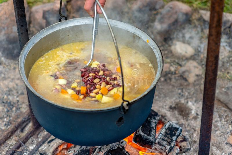 Cooking food in a pot on campfire. Summer camping concept. royalty free stock photography