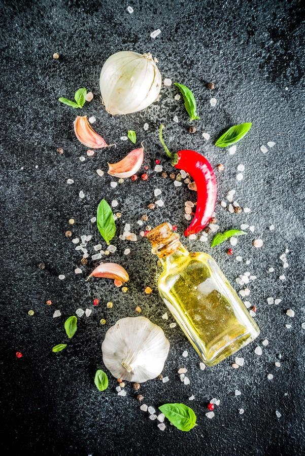 Cooking stone concrete background with spices. Cooking food stone concrete background with spices, olive oil, garlic, onion, pepper, herbs, basil. Top view copy royalty free stock image